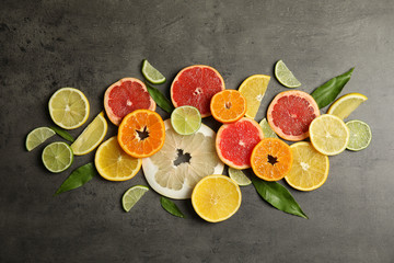 Different citrus fruits on grey background, top view