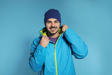 In de dag Wintersporten Young man wearing warm clothes on color background. Ready for winter vacation