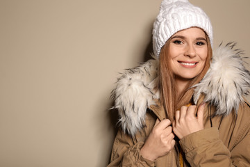 Young woman wearing warm clothes on color background, space for text. Ready for winter vacation