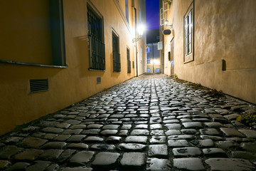 Fotomurales - Old narrow street in Prague, Mala Strana, late in the evening with street lights