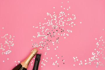 Champagne bottles with confetti stars on pink background. Copy space, top view