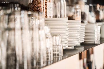 glasses and plates on the shelves of  a stylish modern restaurant.
