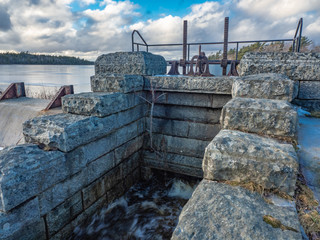 Stone water gate in winter on edge of lake, water flow valve, winter.