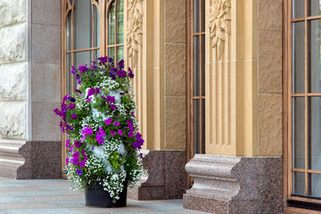 A tall pot with different flowers with white and purple blossoms stands near the building in retro style.