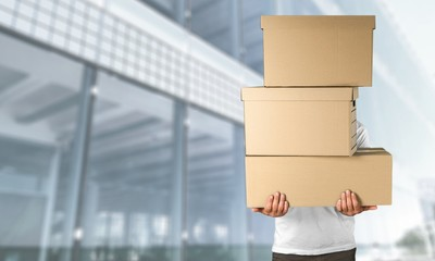 Delivery man carrying stacked boxes in front of face against