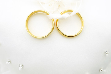 Gold wedding rings on ring pillow with copy space