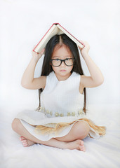 Adorable little Asian girl lying on bed and place hardcover book on her head and looking camera over white background.