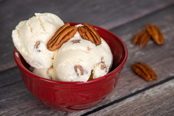 Delicious butter pecan ice cream served in a red bowl. Vintage wooden table background.