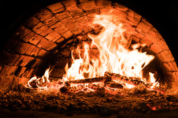 Fire in the oven. Dark background. Concepts of cooking on a fire in the oven. Pizza in the coals. Close up.