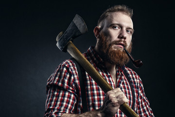 Lumberjack brutal bearded man in red checkered shirt with a smoking tube and axe on dark background