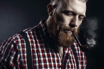 Handsome man or lumberjack, bearded hipster, with beard and mustache in red checkered shirt with smoking pipe