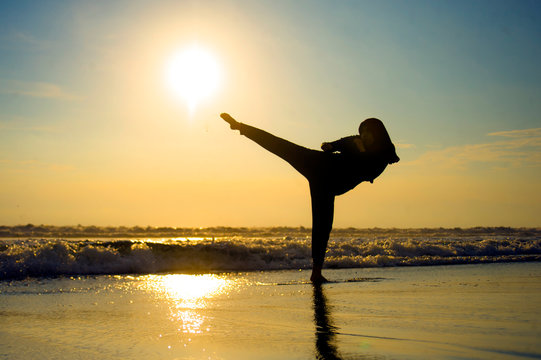 silhouette of young fit Muslim woman covered in Islam hijab head scarf training martial arts karate kick attack and fitness workout at beautiful beach sunset
