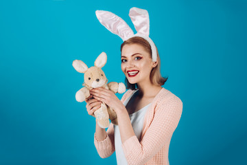 happy woman in bunny ears with toy. Spring holiday. Girl with hare toy. Egg hunt. Easter eggs as traditional food. Happy easter. Woman in rabbit bunny ears. copy space. Funny bunny