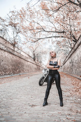 Beautiful biker woman outdoor with motorcycle.