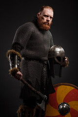 Warrior Viking in full arms with axe on dark background