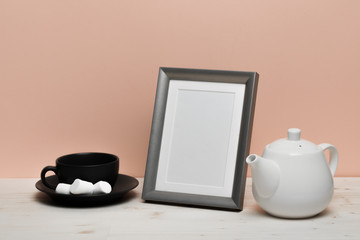 silver frame with mug and teapot on white desk near pink wall
