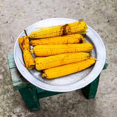 Boiled corn on an aluminum tray. Yellow boiled young corn, usefu