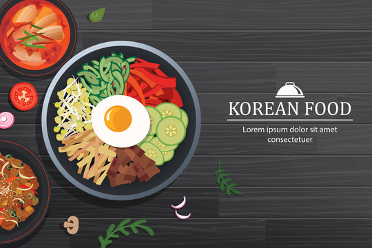 Bibimbap in the bowl on black wood table top view. Korea food background.