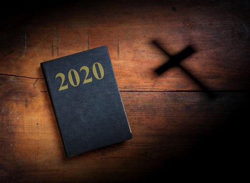 2020 New year. Holy Bible with 2020 text on wooden background. 3d illustration