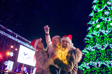 family, christmas, holidays, season and people concept - happy family over lights city background and snow at night