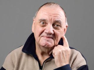 Portrait vieil homme marqué par le temps passé sur fond gris
