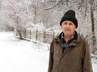 Elderly man standing on the rural street near the fence during a snowfall, pleading expression. Concept of cold weather, snow winter, homeless