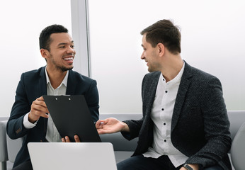smiling business partners discussing a joint commercial project