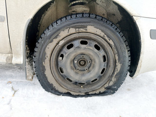 Punched and flat tire on the road. Replacing the wheel with a jack by the driver