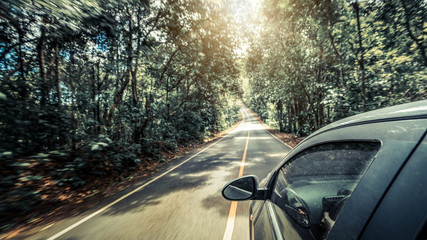 Side view of black car driving on road in forest highway in summer. Travel and explore concept.