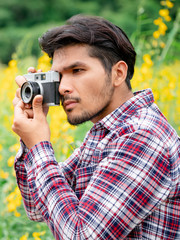 Young hipster man taking photo with old style camera with nature landscape background. Retro and vintage photography concept.