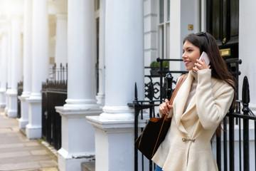 Attraktive Geschäftsfrau mit Mobiltelefon steht auf einer Straße in London mit typisch Viktorianischen Häusern