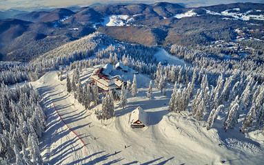 Wooden chalets and spectacular ski slopes in the Carpathians,Panoramic view over the ski slope Poiana Brasov ski resort,Transylvania,Romania,Europe,Pine forest covered in snow on winter season Wall mural