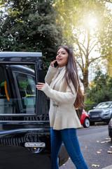 Attraktive Geschäftsfrau mit Handy in der Hand steigt in ein schwarzes Taxi in London