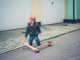Little toddler with scooter in the road