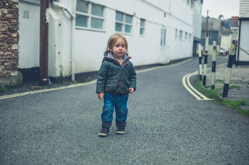 Little toddler standing in the road