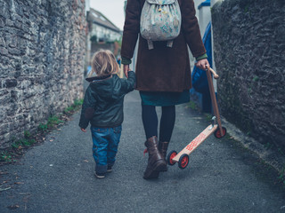 Toddler walking with mother carrying his scooter