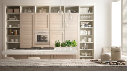 Wooden vintage table top or shelf with candles and pebbles, zen mood, over modern white kitchen with wooden details in contemporary luxury apartment, architecture interior design