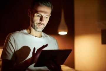 Focused man using tablet at night