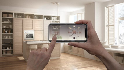 Remote home control system on a digital smart phone tablet. Device with app icons. Interior of modern white kitchen in luxury apartment in the background, architecture design