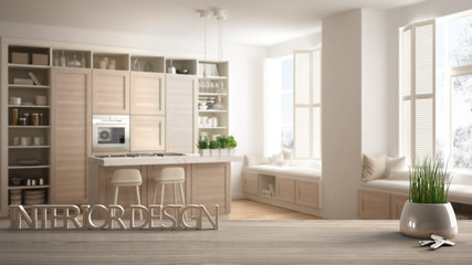 Wooden table, desk or shelf with potted grass plant, house keys and 3D letters making the words interior design, over modern white kitchen, project concept background