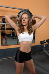 Young and beautiful woman working out with dumbbells in gym - Image