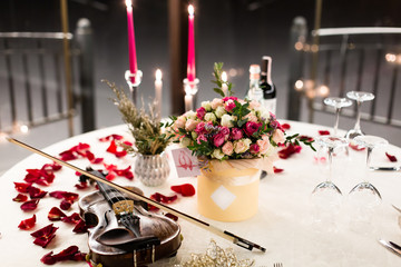 Romantic valentine table setting with wine, dishes, beautiful flowers in box, empty glasses, rose petals, candles, violin