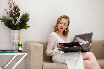 The girl in a beautiful dress looks journal on the couch