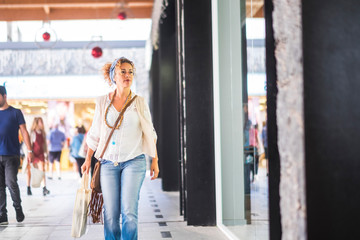 Beautiful 40 years old caucasian lady walking in commercial center mall with shopper bag - trendy fashion woman in shopping stores looking for last fashion trendy stuffs to buy and wear