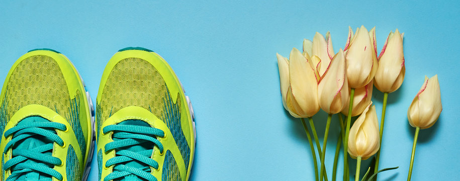 Pair of sport shoes and yellow tulips bouquet on colorful pastel background. New sneakers on blue paper, copy space. Overhead shot of running foot wear. Top view, flat lay