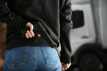 Woman hiding gun behind back outdoors