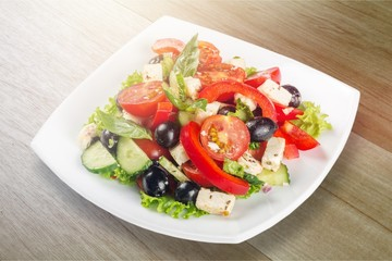 Wall Mural - Greek salad with fresh vegetables on white background