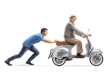 Young guy pushing an elderly man on a vintage scooter