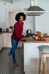 Woman standing in kitchen, preparing food