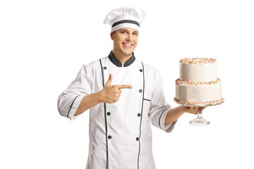 Cheerful male chef holding a cake and pointing at it